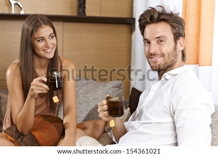 Attractive couple sitting on sofa at home, drinking tea, smiling happy. - stock photo