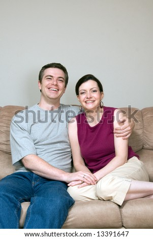 Attractive couple sitting on their living room couch with their arms around each other. Both are smiling at the camera. Vertically framed shot. - stock photo