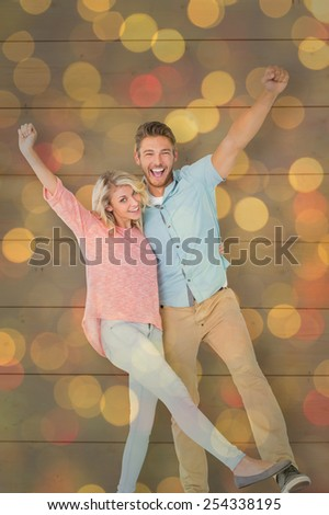 Attractive couple smiling and cheering against close up of christmas lights - stock photo