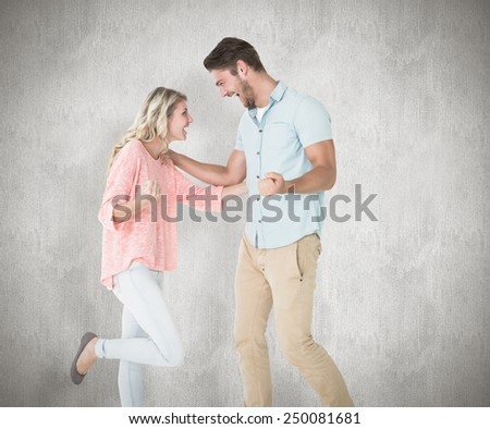 Attractive couple smiling and cheering against white background - stock photo