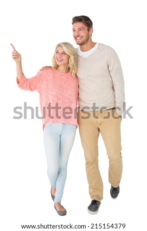 Attractive couple smiling and walking on white background - stock photo