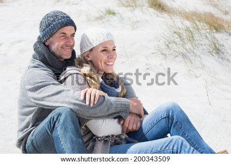 Attractive couple smiling on the beach in warm clothing on a bright but cool day - stock photo