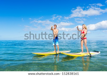 Attractive Couple Stand Up Paddling in Hawaii - stock photo