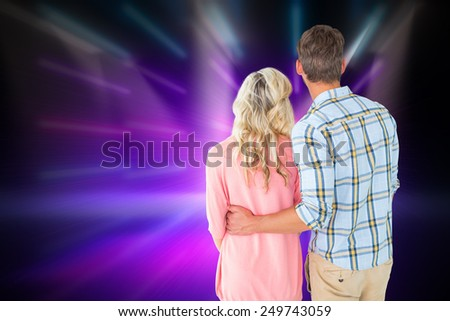 Attractive couple standing and looking against cool nightlife lights - stock photo