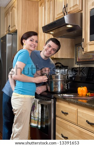 Attractive couple standing by the stove in the kitchen and smiling at the camera. Vertically framed shot. - stock photo