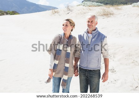 Attractive couple standing holding hands on the beach on a bright but cool day - stock photo