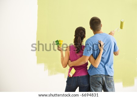 Attractive couple standing in front of partially painted wall with arms around each other. - stock photo
