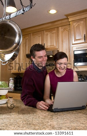 Attractive couple standing in their kitchen and reviewing something on their laptop screen together. Both are looking at the screen and smiling. Vertically framed shot. - stock photo