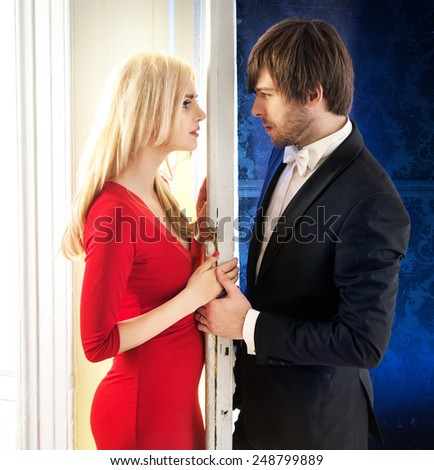 Attractive couple standing next to a white door - stock photo