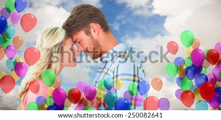 Attractive couple standing touching heads against blue sky with white clouds - stock photo