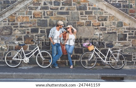 Attractive couple standing with bikes on a sunny day in the city - stock photo