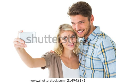 Attractive couple taking a selfie together on white background - stock photo