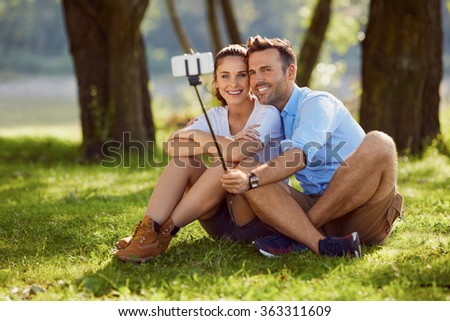 Attractive couple taking selfie with selfie stick - stock photo