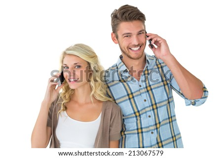 Attractive couple talking on their smartphones on white background - stock photo