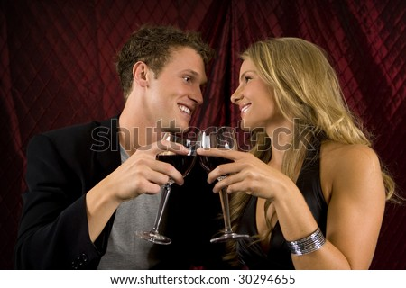 Attractive couple toasting with wine - stock photo