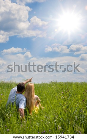 Attractive couple together on meadow in sunny day - stock photo