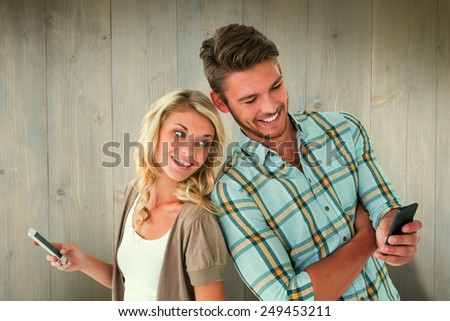 Attractive couple using their smartphones against wooden planks - stock photo