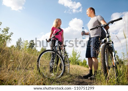 Attractive couple walking after biking and drinking water in the forest - stock photo