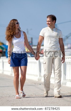 Attractive couple walking along pier. Young man and young woman on seashore