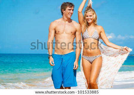 Attractive Couple Walking on Beautiful Beach - stock photo