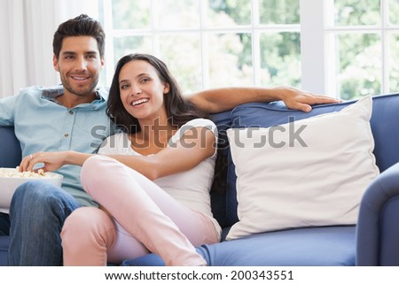 Attractive couple watching tv on the couch at home in living room - stock photo