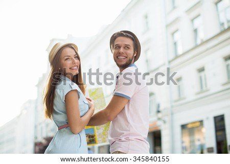 Attractive couple with a map outdoors - stock photo