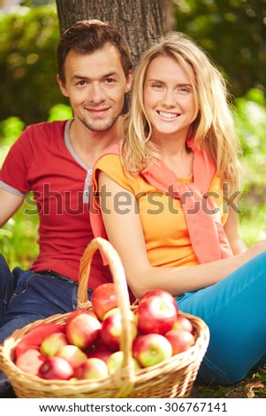 Attractive couple with basket full of red apples sitting by tree - stock photo