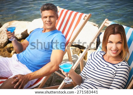 Attractive couple with cocktails sitting on deckchairs by the sea - stock photo