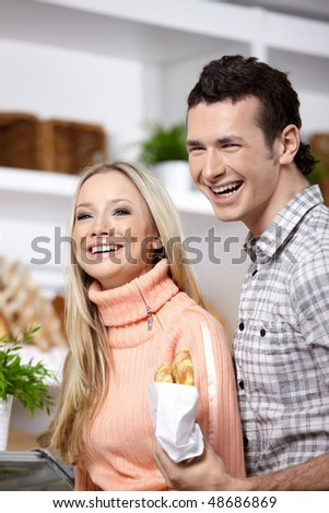 Attractive couple with rolls in shop - stock photo