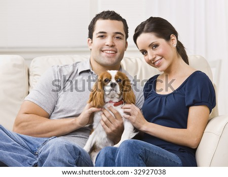 Attractive couple with their dog on their living room couch. horizontal - stock photo
