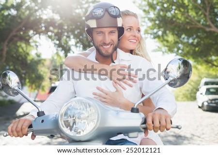 Attractive couple with their scooter on a sunny day in the city - stock photo