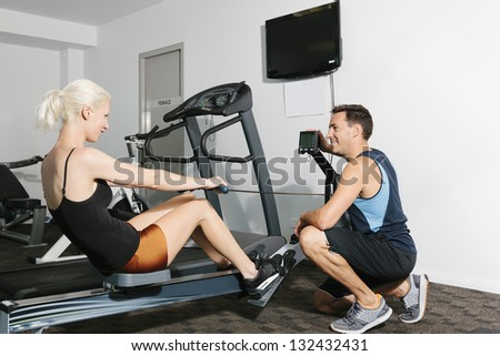 Attractive couple working out in gym - stock photo
