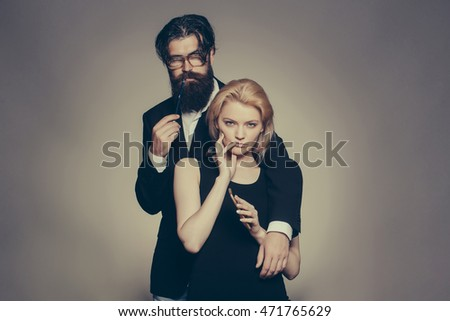 Attractive couple young blonde serious woman with pretty face holding cellphone and handsome bearded sexy man in glasses standing behind her posing in studio