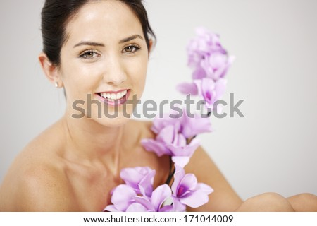 Attractive crop of a woman's face smiling holding purple Orchid's