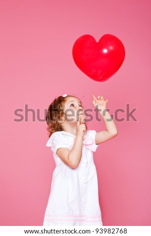Attractive curly girl playing with heart shaped balloon - stock photo