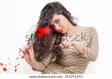 Attractive curly hair girl with glowing cupid wand and hearths pointing and looking at camera  - stock photo