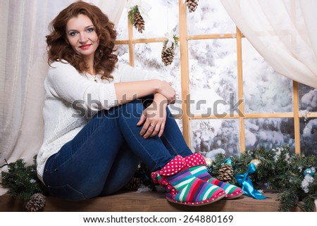 Attractive curly woman sitting on the windowsill - stock photo