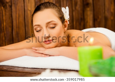 attractive cute girl lying in spa with closed eyes near the candles - stock photo