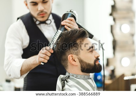 Attractive dark haired man wearing white shirt doing a haircut with hair dryer and hair brush for man with black hair at barber shop, mirror at background.