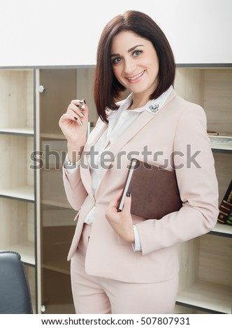attractive dark-haired woman dressed in a beige suit standing near the table in the office and holding a notebook and pen. Business lady looking at the camera