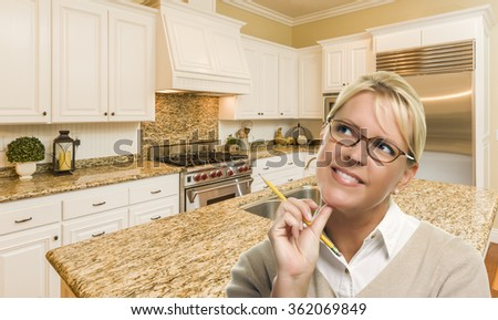 Attractive Daydreaming Woman with Pencil Inside Beautiful Custom Kitchen. - stock photo