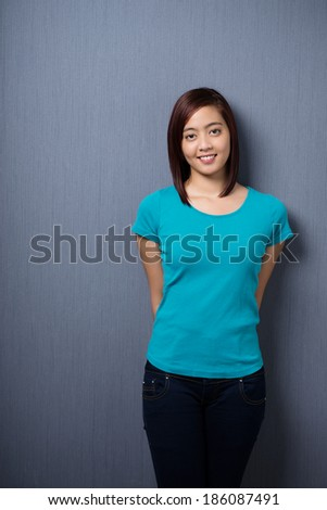 Attractive demure young Asian woman standing with her hands behind her back against a dark studio background with copyspace smiling at the camera - stock photo