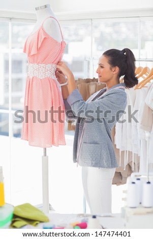Attractive designer fixing dress on a mannequin in a studio - stock photo