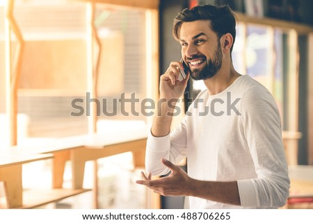 Attractive designer in casual clothes is talking on the mobile phone and smiling while working in his studio