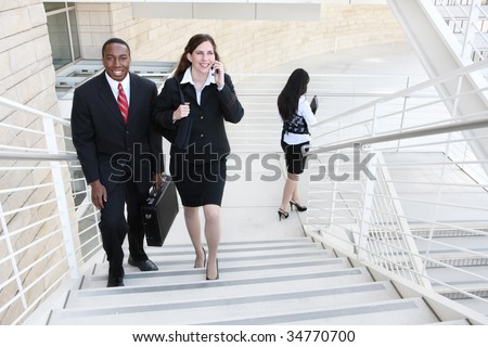 Attractive diverse business man and woman team walking up stairs to work - stock photo