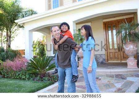 Attractive diverse family outside their home having fun - stock photo