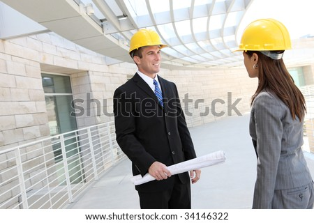 Attractive diverse man and woman architect team at building site - stock photo