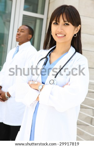 Attractive, diverse medical man and woman team at hospital - stock photo