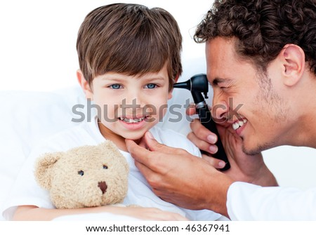 Attractive doctor examining patient's ears at the hospital - stock photo