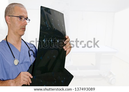 attractive doctor looking x ray in hospital background - stock photo